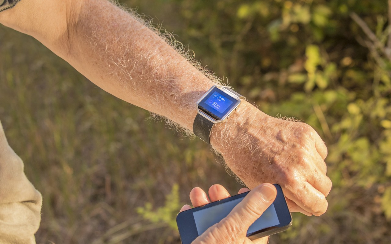 Man with smart watch and mobile phone looking at pedometer results